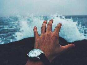 時計をした手と海