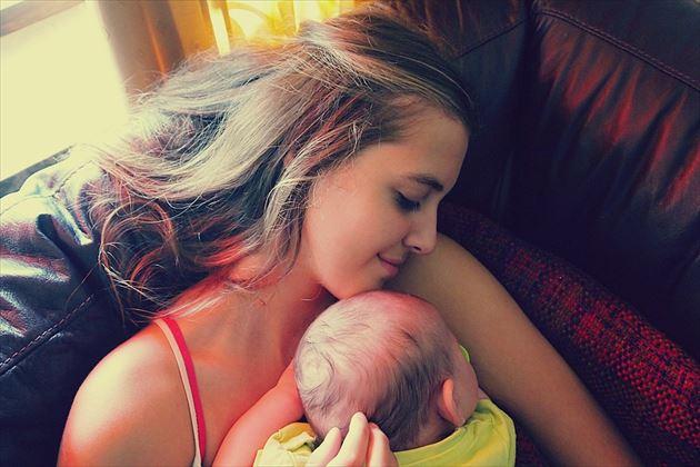 眠る赤ちゃんを抱っこする女性