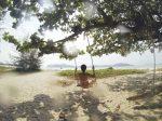 世界一絶景のビーチでブランコに乗る女性の画像