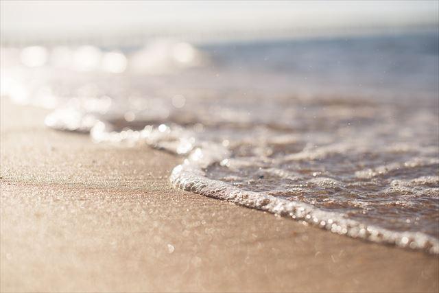 砂浜に打ち上げる波の画像
