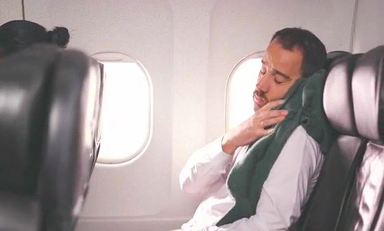 飛行機のイスで仮眠できずに困っている男性の画像