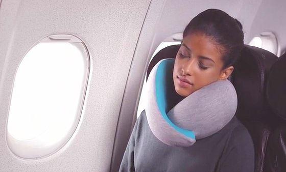 飛行機でオーストリッチピローゴーを首につけて仮眠する女性の画像