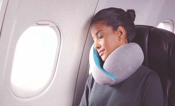 オーストリッチピローゴーを使って快適に飛行機内で仮眠をとる女性の画像
