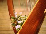 花が添えられた美しいハープ楽器の画像