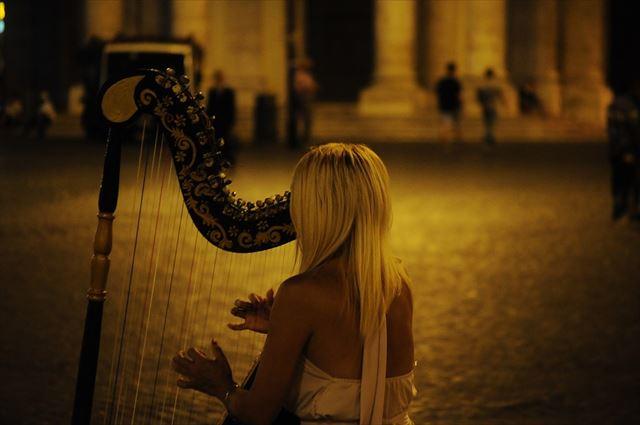 ハープで美しい音色を奏でる女性の画像