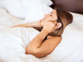 おすすめのイヤホンをして眠りにつくベッドの女性の画像