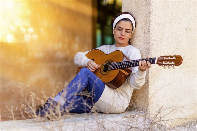 クラシックギターで音楽を奏でる女性の画像
