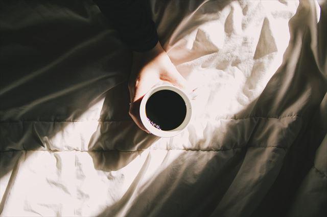 ベッドの上で目覚めのコーヒーを飲む人のが画像