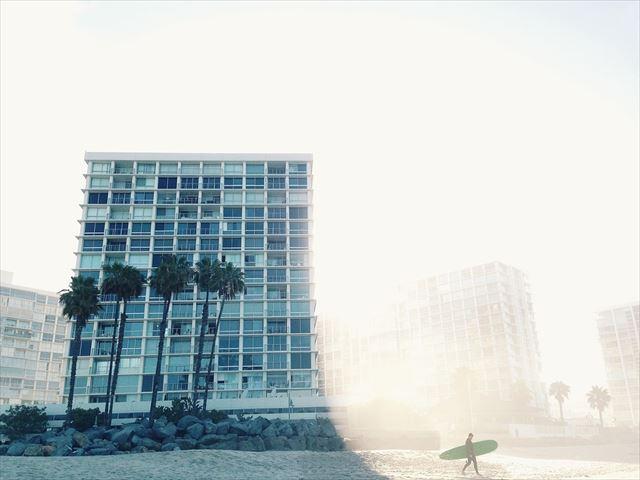 朝陽とともにサーフィンにむかう人の画像