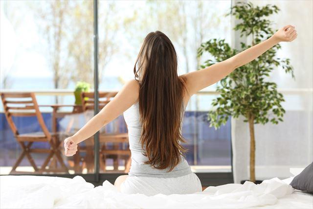 朝の音楽で気持ちよく目覚める女性の画像