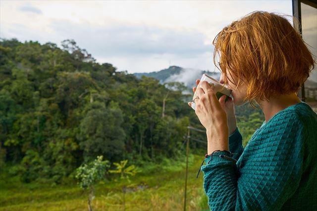 朝音楽を聴きながらコーヒーを飲む女性の画像